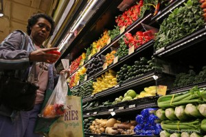 Community resident selecting produce in new Whole Foods grocery store.