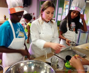 Chef instructs two youth cooking students.