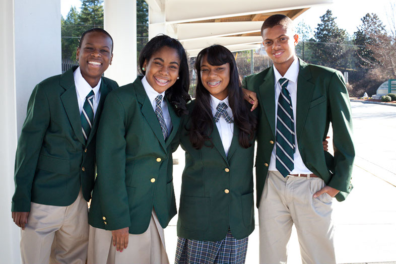 Four Drew Charter School students in the Villages of East, standing outside the school.